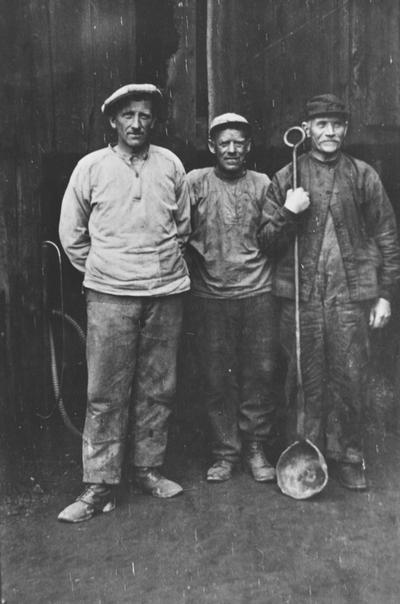 Tre arbeidere ved Røros smeltehytte med smelteøse