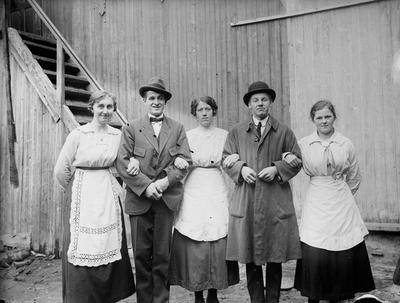 Gruppeportrett av fem personer: Tre kvinner i serveringsforkle og to menn i hatt og frakk