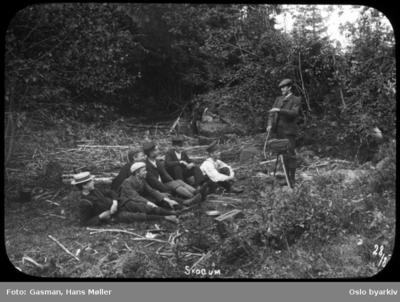 En gruppe menn sitter på bakken foran en fotograf