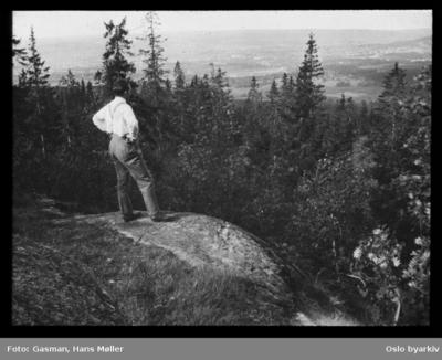 En mann som ser på utsikten fra et berg eller en kolle i skogen