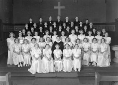 Gruppebilde av konfirmanter og prest i Rolvsøy kirke