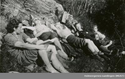 Ungdommer soler seg ved en bergeknaus