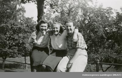 Tre kvinner sitter på et gjerde