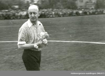 Mann med blomsterbukett ute på en fotballbane