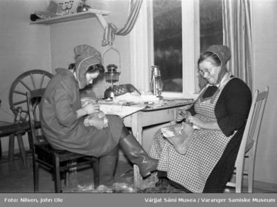 To kvinner sitter innendørs og syr skaller
