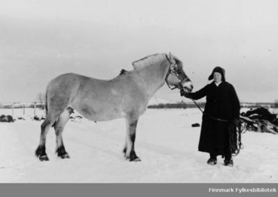 Et fotografi av Magna Erika stående ved siden av en hest