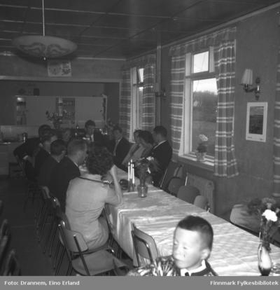 Mange personer sitter ved et langbord i et lokale i Neiden