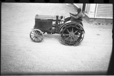 Mann på traktor av merket Deering utenfor Lena stasjon