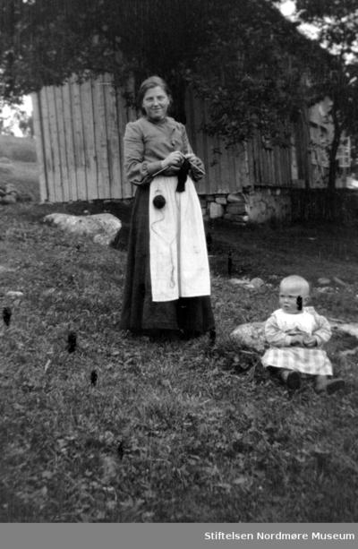 Fotografi av en strikkende kvinne sammen med et lite barn