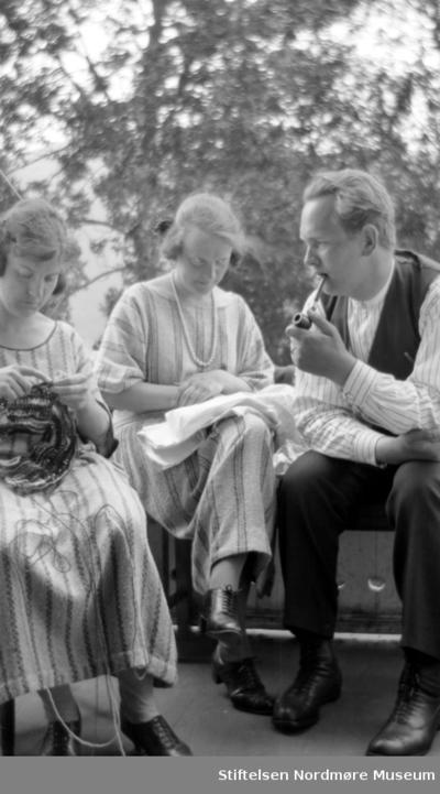 Fotografi av to kvinner og en mann sittende ute på en veranda