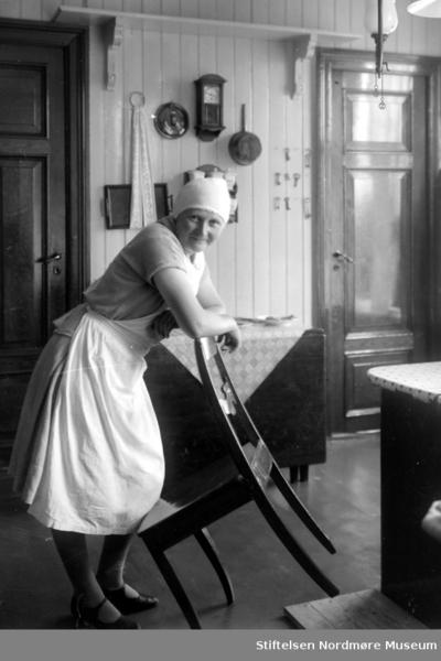 Foto av en kjøkkenkvinne (tjenestepike?) stående på et kjøkken hvilende på en stolrygg