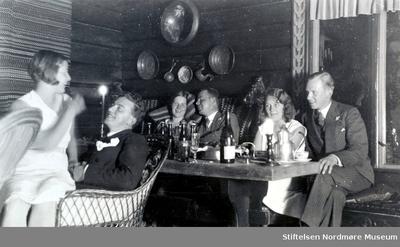 Foto av en gruppe mennesker i hyggelig selskap inne i en hytte