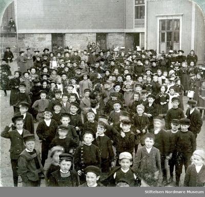 Del av et stereofoto som viser en større gruppe barn ute på en skoleplass