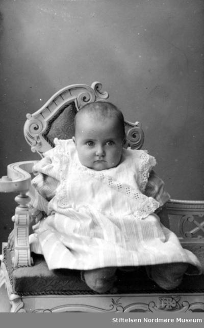 Portrett av en baby sittende på en stol