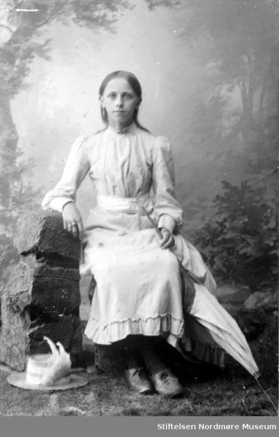 Studioportrett av en ung kvinne iført en fin sommerkjole