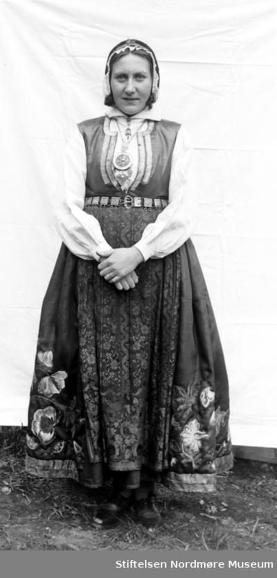 Kvinne kledd i Nordmørsbunad med skjørt med broderte blomster og damask- forkle