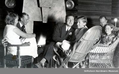 Foto av en gruppe mennesker foran peisen i en hytte