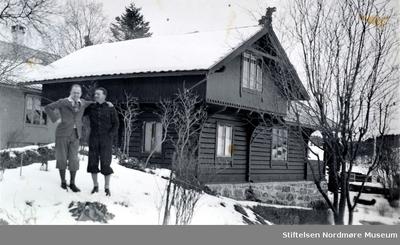 Foto av to menn foran ei hytte en vinterdag