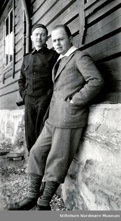 Foto av to menn foran ei hytte