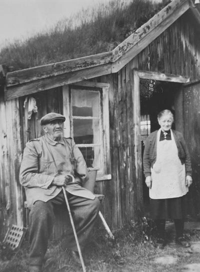 Portrett av eldre ektepar foran eldhuset på setra Pustbakken på Glåmos