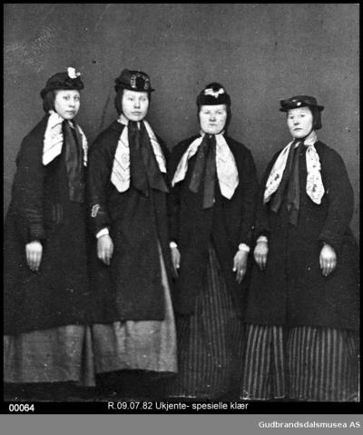 Fire kvinner i fine klesdrakter