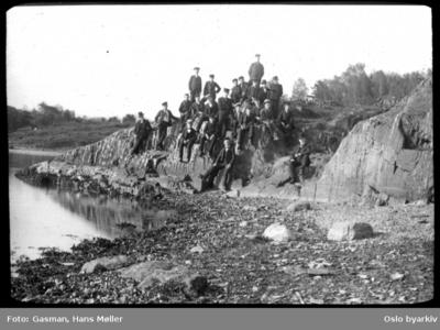 En gruppe menn og ungdom på stranden på Hovedøya