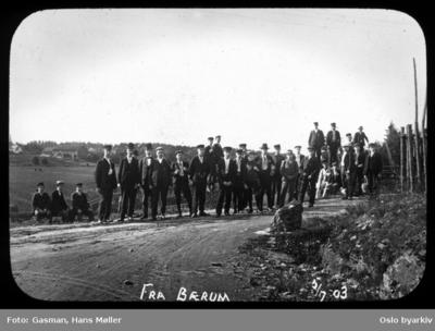 En gruppe menn og ungdommer poserer for fotografen i et veikryss