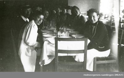 Jenter og gutter i russedrakt sitter rundt et dekt bord