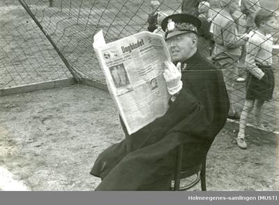 Politimann sitter og leser Dagbladet i et fotballmål