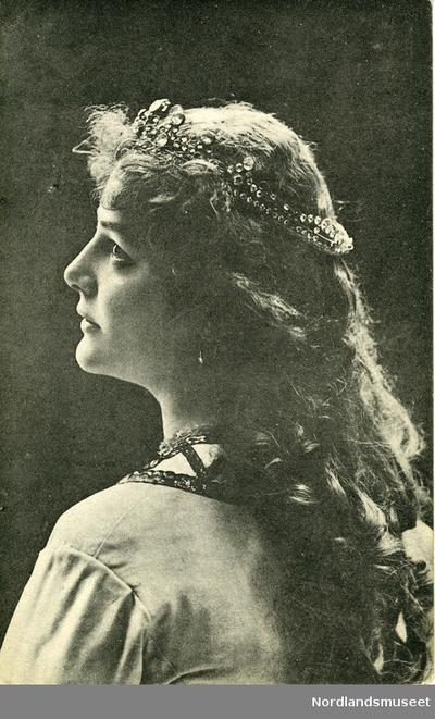 Postkort med portrett av overkroppen til en kvinne, vendt med ryggen mot kamera og hodet i profil. . Hun har et diadem i håret, langt, krøllete hår og brodert krage på kjolen.