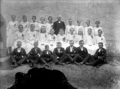 Konfirmandgrupp, sannolikt vid Vallby kyrka (östra gaveln), Uppland. I mitten sannolikt kyrkoherde Gustaf Thegerström (1853-1937). Se mer under historik.