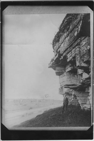 'Diverse foton från sannolikt Kinnekulle. Kalkbrott och naturliga skärningar. :: Man står under vittrad klippbrant med slättlandskap i fonden. ::  :: Serie fotonr 4885-4901.'