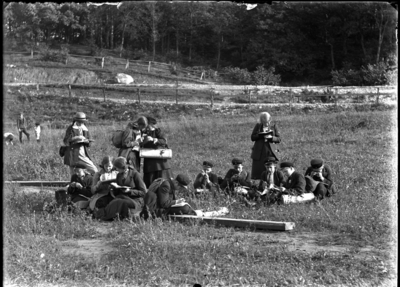'Gruppbild med 6 pojkar och 7 flickor sittande och stående på öppen gräsmark ev. betesmark. Pojkarna iklädda keps, skärmmössa liksom även 1 flicka. 2 av flickorna iklädda hatt resp. mössa och övriga utan huvudbonad. Flätor. Kappa. Klänning. Kjol. Eleverna på exkursion, utflykt och arbetar med böcker och ev. lupp. Skriver och läser. I bakgrunden ytterligare 1 pojk och 2 mindre barn. I bakgrunden 2 trästaket, innanför bortersta växer lövträd och är ev. betesmark. Ev. väg mellan trästaketen, hagarna. Se även fotonr. 5137:17. ::  :: Ingår i serie med fotonr. 5137 med diverse bilder. Plåtarna ligger i 2 pappaskar. På asken för negativen 9x12 cm och 12x18 cm står texten: ''Fröken Pettersson, Eksjö. Kopieras. Negativ. Alingsås samskola? m.m.'''