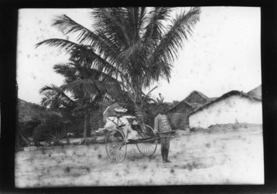 'Diverse fotografier från bl.a. dåvarande Nordrhodesia, nu Zambia, tagna av Konsul Magnus Leijer. ::  :: 1 st kvinna med parasoll sittande i en vagn dragen av 1 st man. Bakom dem är byygnader och träd synliga.'