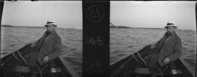 'Bildtext: ''Romney vid rodret.'' :: I förgrunden båt med 1 man i fören, hattklädd och med pipa. ::  ::  :: Ingår i serie med fotonr. 5261:1-14. Se även hela serien med fotonr. 5237-5267.'