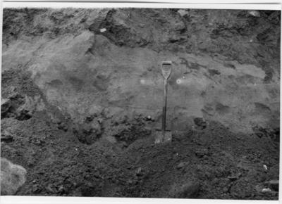 'Närbild på vägg i grustaget, en spade står i grusen. :: Beskrivning av den subfossila mammutbeten: längd 360 mm, diameter 70-80 mm. ''Fyndet har vid bärgningen fallit sönder i 5 större och ett flertal mycket små bitar. ::  :: Ingår i serie med fotonr. 7053:1-11. Se även fotonr. 2023-2027 och 2958.'