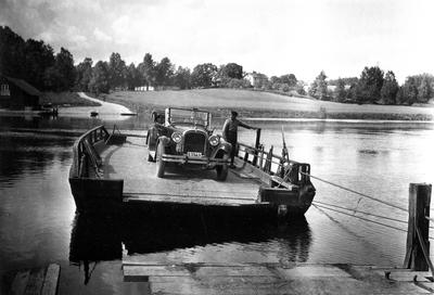 Högsäters färja över Byälven vid nuvarande väg 175. Redan 1710 förekom transporter över Byälven vid Högsäter och den finns kvar än idag och är dessutom den sista återstående vägfärjan i Värmland. Bilen är en Dodge Touring från 1925 och ägdes då av Gustaf Warolin i Säffle.