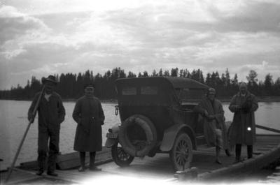 David Brundin hälsar på Elis Öhrn, som står vid färjekarlen till vänster, i chaufförsmössa. Elna och David Brundin till höger. Bilen en Overland 1924 med 4 cylindrar.