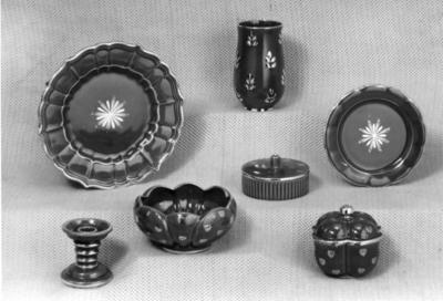 Dekor: Rubin, skaparen var chefdekoratör Eugen Trots, anställd på Gefle Porslin 1922-1963. Dekoren var i produktion 1940-1958, består av handmålade spridda guldornament på bränd rubinröd glasyr.  Vas modell FW 1939-1952 höjd 16,5 cm,(A-L. Thomson.) frukttallrik modell U 1933-1957 diameter 17 cm, (A. Percy.) Frukttallrik modell W 1933-1955, höjd 18 cm, (A. Percy.) bonbonjär modell A 1941-1957, höjd 11,5 cm. (A. Percy.) Skål modell DT 1936-1955 diameter och höjd 17x9 eller 26x11 cm. bonbonjär modell R 1939-1955 höjd 7 cm, ( H. Östergren)