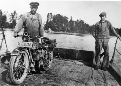 Södra Färjsundet. Färjkarlen Per Olof Pettersson med son. Fotot taget på 1920-talet, färjan roddes då med åror. Motorcykeln tillhörde skolkökslärarinnan Astrid Brundin (dotter till kyrkoherden). Det var även då ovanligt med kvinnliga motorcykelförare.