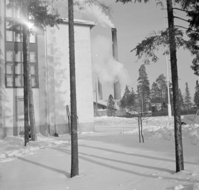 Exteriör vid F 19, Svenska frivilligkåren i Finland. Del av byggnad och träd. I bakgrunden syns Kemi pappersmassefabrik.