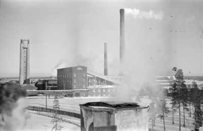 Pappersmassefabriken i Veitsiluoto vid F 19, Svenska frivilligkåren i Finland. En man och en skorsten syns i förgrunden.