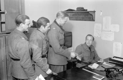 Utbetalning av lön till militärer tillhörande F 19, Svenska frivilligkåren i Finland. Tre män i kö till löneutbetalare vid skrivbord.
