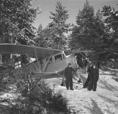 Flygplan Waco ZQC-6 mekas vid värn, vid F 19, Svenska frivilligflottiljen i Finland. Tre militärer vid flygplansmotorn.