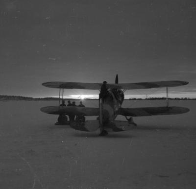 Flygplan Gloster Gladiator startar i motljus från F 19, Svenska frivilligkåren i Finland. Fem militärer i arbete.
