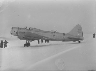 Sovjetiskt flygplan Iljushin DB-3 står på ett fält under finska vinterkriget, 1940. Människor i rörelse runtomkring. Bild från F 19, Svenska frivilligkåren i Finland.