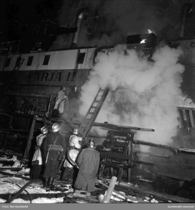 Brandmän släcker en brand på Alnöfärja II som ligger upplagd vid Mohögs slip för reparation.