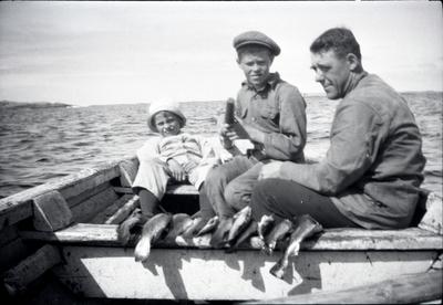 En man med två barn i en fiskebåt, 1920.
