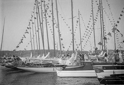 Segelregatta i samband med GKSS (Göteborgs Kungliga Segelsällskap) 75-årsjubileum 1935. Segelbåtarna ligger i hamnen och är prydda med flaggspel (s.k. flagg över topp).
