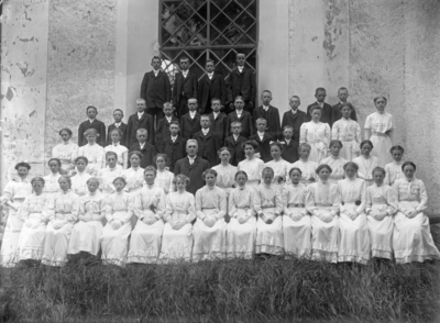Konfirmandgrupp vid Simtuna kyrka, Uppland. I mitten kyrkoherde August Hylander (1852-1935).